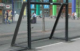 Stainless steel cable mesh are mounted to a black steel frame to create a ball catcher.
