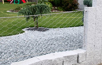 Stainless steel garden fencing mounted to stone base and columns are designed to protect your prized garden plants.